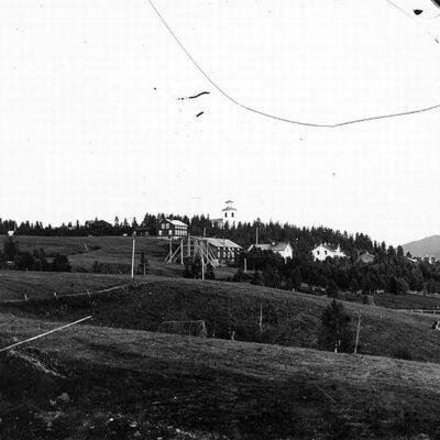 I förgrunden MoDo:s faktorsbostad. Gården är numera nerbrunnen. Har ägts av jägmästare Berg, faktor Nordfjell, fabrikör Carl Jaede. Carl Hugo Jaede arbetade åt MoDo. Husen tillhörde MoDo innan de flyttade till Bjurholm. Stora byggnaden var förvaltarbostad. Vinkelbyggnaden var arrendatorsbostad. Överst till vänster bagar Gustavssons gård. I skogen till vänster skolan, Till höger i bakgrunden Hedins gård. Lilla vita huset till höger en tvättstuga byggd av MoDo. Bilden är även utgiven som vykort