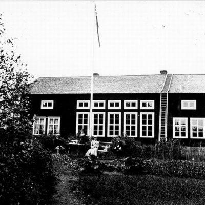 Skolan sedd från baksidan.  Till höger bagare Gustavsson, till vänster skollärare Lundqvist. Flickan, bagarens dotter Frida, senare gift med faktor Almqvist förvaltare hos MoDo. Notera den fina trädgården