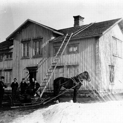 """""""Bolagsboa"""", se """"Örträsk och dess historia del 2"""".  Fotot förmodligen taget strax efter att J.Valfrid Persson (Ekehjelm), från Fredrika, år 1898 förvärvat fastigheten och butiken.  Nr 2 från vänster handlare Ekehjelm. Han hette Person men tog namnet Ekehjelm. Kom från Fredrika. Han har besök från Fredrika som nu är på väg hem efter en påskhelg."""