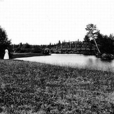 Gamla bron över Öreälven i övre änden av sjön. Fotot taget nedanför bron och visar en del av de slåtterängar som bönderna vid den tiden hade långt upp efter Öreälven.
