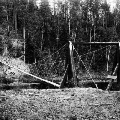 """Hängbron över """"strucka"""", som betyder starkt strömmande vatten utan fors, Öreälven, nedströms Storforsen. Hängbron byggdes under 1920-talet för att underlätta kommunikationerna för skogsarbetare. Jägmästare Åke Berg tjänstgjorde i Örträsk vid denna tid och var eventuellt initiativtagare."""