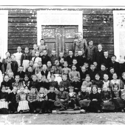 """April 2007 Ett skolkort från 1895 i Örträsk Avskrift från tidningsurklipp från VK, troligen infört någon gång på 1960-talet: Örträsk gamla skola.  Bilden som insänts av Jonas Oskar Eriksson, Stöckeby, visar 1895 års elever vid Örträsk gamla skola i Östra Örträsk. två klassrum hade den men rymde ändå bara """"storskola"""" och """"lillskola"""". Folkskolläraren hette Wiklund och småskollärarinnan, Hulda Andersson. I första och andra raden, något till vänster på bilden (se markeringarna) återfinnes Eriksson själv, samt hans blivande fru, Agnes Näslund. """" Kommentarer av undertecknad, som har gjort den numrerade skissen: För några år sedan fick jag en kopia av originalfotot av J. O. Erikssons sondotter, Siv Eriksson-Marklund, och det har gjort att ytterligare några elever kunnat identifieras. Nr 5. Jonas Oskar, nr 20. Agnes, nr 16. Edit Strömgren, bröderna Örestigs mor (gift med Per Persson), Klara Perssons bror, nr 30. Elma Rehnman (dotter till handlanden Rehnman), nr 34. (i randig klänning),  Klara Persson (med tiden blev hon fotograf), nr 36.(t.h.) Emmy Hellgren (gift med Johan Königsson, V. Örträsk),  nr 39. och 40., systrarna Hedvig och Hilma Jonsson (Hilma blev lärarinna för klasserna 3 och 4 i samma skola), och nr 53, deras bror, Albert,  nr 57. Amanda Sjölund, (gift med Helmer Strandberg), nr 63. Nils Viktor Königsson.Lärarna bör vara nr 69 och 70. Betr. skolbyggnaden: Till det yttre är den fortfarande i stort sett oförändrad sedan den byggdes på 1860-talet, särskilt på baksidan, som man kan se av ett foto från sekelskiftet 1800-1900. På framsidan fanns separata entréer till de båda skolsalarna och längst till höger ingång till lärarnas bostäder, som med tiden blev obehövliga. Från 1913 placerades """"småskolan"""" i den mindre byggnaden intill den stora  Under 1950-talet kom vinkelbyggnaden till, med gymnastiksal och med skolbespisningslokal. Då gjordes också en omfattande ombyggnad av interiören, med lokaler även på övervåningen och med en gemensam entré, längst till höger mot """