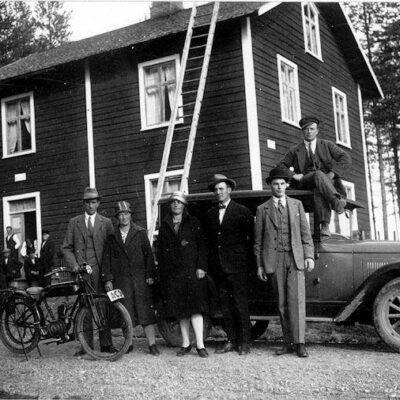"""Februari 2006 Vilket hus är detta? (Visst står huset fortfarande kvar på Västra?) Vilka är personerna? Vem ägde bilen? Vem ägde motorcykeln och vem sitter på den? Vad är det för vita skyltar på huset? Bilderna är troligen tagna av Sigvard Edlund och kan vara fotograferade 1928.  Om fotografen hette Sigvard Edlund, finns det någon som känner till honom? Bodde han här i trakten, eller? 060216 Från Hans Gustavsson har mail inkommit med följande: Det är nog fotografen själv som sitter på motorcykeln, dvs Sigvard  Edlund, Bjurholm. Jag har läst om Sigvard Edlund för många år sedan i en tidskrift som  ges ut av Västerbottens museum. Han bodde enligt vad jag minns i  Bjurholms socken, möjligtvis Näsland. Allt om Sigvard och hans bilder finns i denna tidskrift. ##### 060216 Från Sivert Nyström kommer följande information: Bilden till höger föreställer Sigvard Edlund på Viktors lättviktare på Viktor Königssons gård i Örträsk. Bilden tagen 1928. Från Sigvard Edlunds fotosamling, Öredalen, Bjurholms socken ##### 060223 Göran Jakobsson meddelar via telefon: att huset inte är Viktor Köningssons utan tillhörde Johan Königsson. De vita skyltarna är nog skyltar som talar om att telefonväxel finns i huset. ##### 060223 Från Margareta Dahlgren kommer ytterligare information: Huset felaktigt uppgivet som Viktor Königsons. Rätt är att det är Johan Königsons, Västra Örträsk. Huset bebos numera av Greta Königson, Johan Königsons sonhustru, och det är oförändrat, så när som på att nu finns en farstukvist och att huset är brädfodrat. ##### 060314 Från Rune Königsson i Torshälla kommer mycket information: Detta hus var Runes föräldrahem och han och hans bröder syns också på bron framför huset. På de vita skyltarna stod ordet """"Rikstelefon"""" och under Runes uppväxt var fyra abonnenter anslutna till denna växel. Motorcykeln på bilden tillhörde Ferdinand Lindström. Motorcykeln var en remdriven maskin och hade registreringsnummer """"AC 34"""" och dess efterträdare var en """"riktig"""" motorcykel med sidova"""