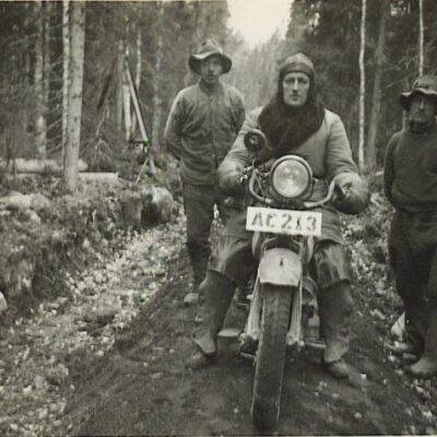 """Januari 2007 Denna bild ägs av Ann-Marie Boman och har skannats av Örjan Jacobsson.  Från Hans Gustafsson kommer följande: Han som sitter på motorcykeln liknar kronojägare Gustav Jonsson.  Motorcykeln är troligtvis en HD för de var populära i byn en gång i tiden. Det byggdes många cykelvägar under trettiotalet då tiderna var dåliga. Jag tror att de kallades """"enkronas-vägar"""" för så litet kostade det att anlägga en meter väg. Valdemar Astergren, J O Jonsson, Efrid Jonsson och Gustav Jonsson var bröder och alla var  storväxta. I Efrids loge stod motorcykeln när """"Kron-Gustav"""" ej var  ute på tjänsteresor. Gustav besvärades av sina ben och att åka motorcykel var inte alltid så lätt för honom. Han övergick så småningom till att köra bil, en PV. Från Henry Eriksson kommer en gissning: Om inte mitt minne sviker mig så tror jag att det är kronojägare Gustav Jonsson från Örträsk som sitter på sin motorcykel. Om jag gissat rätt så vill jag återkomma till Gustav och hans motorcykel, det gäller en händelse som inträffade 1928. Flera andra har också påpekat att det ska vara Gustav Jonsson. Motorcykeln är förmodligen inte en HD utan är av märket Indian."""