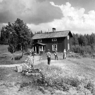 Mars 2017 Höglunda, Nuvarande manbyggnaden, byggd 1911 och nu renoverad. Foto: Evert Larsson 1957 Bilden finns på Västerbottens museum  Fotografiet är taget 1957 och är det någon som känner igen personerna på bilden så hör av er. Från Leif Alperud kommer följande: Detta är mitt barndomshem, och jag kan med hundra procents säkerhet säga att kvinnan till höger är min mor Sanna Alperud. Vilka de andra är har jag ingen aning om, ser att dom bär på något som liknar dokument av något slag. Kan vara sällskap till fotografen. Torpet blev ombyggt 1947 och jag har minnesplaketten i säkert förvar. Pappa och mamma var de sista som lämnade Höglunda 1964, då flyttlasset gick till Örträsk.