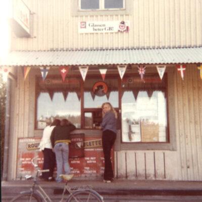 Augusti 2017 En bild från kiosken i Örträsk. Bilden är utlånad av Kari Hammer  Är det någon som har något att berätta om bilden hör av er tillake@runnman.seeller 070-282 00 02 eller skriv i kommentarsfältet här nedanför.  Från Charlotta Öhrman kommer följande:  Kiosken som låg i huset bredvid Sivs affär (Handlarn) ägdes av John och Betty Sandström fram till någon gång i början av 70-talet. John skötte också om minigolfbanan och i kiosken hämtade man ut klubbor och bollar för spel. Intill golfbanan stod den uppstoppade björnen, som numera finns på hembygdsgården. John och Betty drev tidigare under många år konditori och pensionat i huset. Betty Sandström hade dåtidens catering och gjorde bl.a. smörgåstårtor på beställning. Hos Sandströms kunde man också boka större fester och någon gång under min tonårstid serverade jag tillsammans med några kompisar på sådan fester.  Hälsn. Charlotta