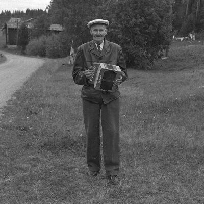 """September 2017 Denna månadsbild är utlånad av Gun Hammer, som säger: Jag tror att det är Karl Oskar Königsson, bror till Johan Efraim Königsson (och min mormors morbror). Karl Oskar Königsson var född 1874 och avled 1951. Jag vet att han spelade dragspel (satt ibland i en båt på sjön och spelade) och jag tror han bodde på vinden i """"andra huset"""" hos Königssons.  Om nu webbmaster har rätt så är detta samme man som var på oktobers månadsbild 2014"""