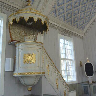 Predikstolen har en tidstypiskt nyklassicistisk utformning med rund korg, lambrequinförsett ljudtak, färgsättning i ljusgrått och guld, och med symboliska motiv som anspelar på lagen och evangeliet samt närvaron av den treeniga Guden. Draperimålningen på väggen är även den utförd av Carl Erik Holmström.