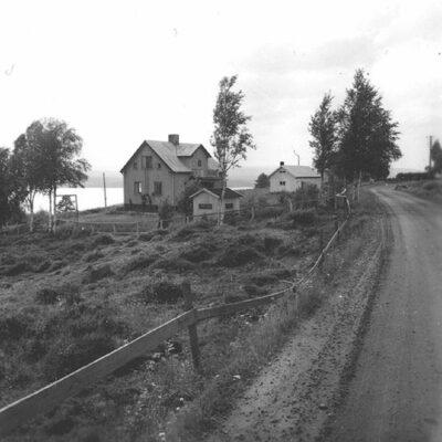 Januari 2013. Detta fotografi är taget av Evert Larsson, Umeå, som levde mellan 1898 och 1964. Är bilden tagen i Örträsk-området? Var i så fall?  Från Sivert Nyström kommer: Januaris månadsbild på Arvid Anderssons fastighet innibyn. Familjen bodde där fram till 1958 då dom flyttade till Lycksele. Man ser att fotot är taget innan den nya vägen byggdes. Jag tror att huset idag används som fritidshus.  Från Agneta Höglund kommer liknande uppgifter.  Vet någon när det vita huset med röda knutar som i dag står bortanför detta hus byggdes? Det vita huset syns inte på denna bild.