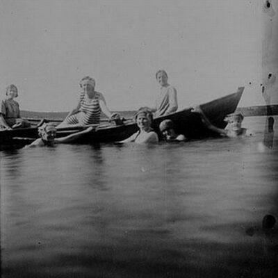 Badbild i Örträsk - på 1920-talet. Sittande i båten, från vänster: Sigrid Öhrman?, Gunborg Gerhardsdotter gift Lundgren, Anna Öhrman. I vattnet: Annie Öhrman?, Selma Öhrman, Sanna Rådström?.