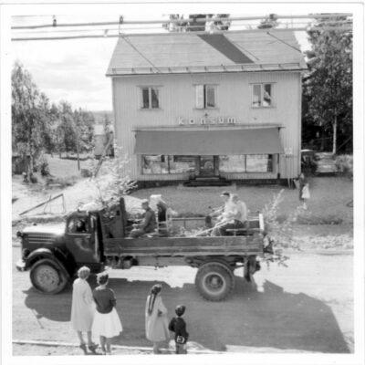 Juli 2006 Foto: Hilding Svensson Månadens bild har kommit från Görel, dotter till Hilding, och hon tror att bilden tagits i samband med en hembygdsfest ev. någon gång på 50-talet. Vägbyggnation pågår men vilket år? Vilka är personerna på lastbilen? Vems är lastbilen? Vilka är åskådarna på trottoaren? Notera även att affärens fasad, då Konsum, genomgått en stor förändring.