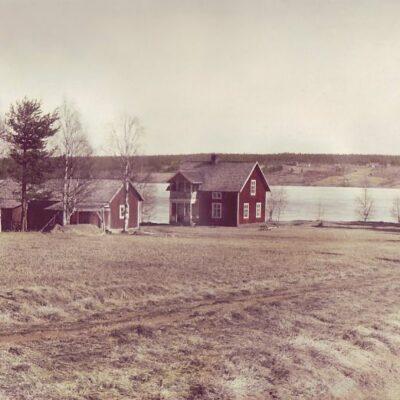 """Juli 2005 En efterlysning! Bilden visar ett hus på """"Oskars-Näset"""" på Västra Örträsk.  Kortet finns hos Karin Svensson. Detta är ej utlagt Vem har tagit bilden? När är den tagen? Vilka är personerna som nämns? Finns det fler uppgifter om huset och personerna som bodde där? Kollar in gamla månadsbilder, när jag upptäcker att våran stuga är med!  Vad jag vet har ingen av de nämnda personerna något med huset att göra, men jag kan ha fel. I detta hus bodde Julia Königsson när hon var gift för första gången. Hon och hennes man tog över det av hennes svärföräldrar, som jag inte minns namnet på just nu. Det såldes senare,minnsej till vem, men jag har det antecknat i stugan någonstans. Kommunen har också haft det i sin ägo, då arbetare som röjde sly runt sjön fick bo där. Därefter tog Lars Bjurenstam över, han avled även där. Dödsboet sålde huset till mig och min man juli 2001. Vi heter Anette och Stefan Dannelöv"""
